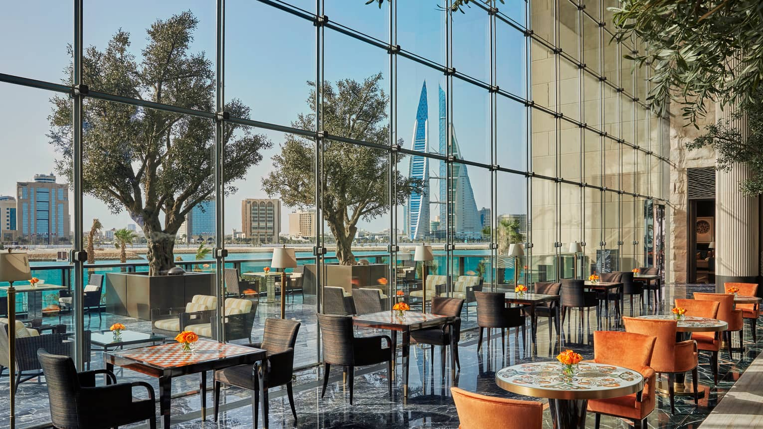 Sunny Bahrain Bay Kitchen dining room with orange and brown chairs, decorative table tops, tall glass wall
