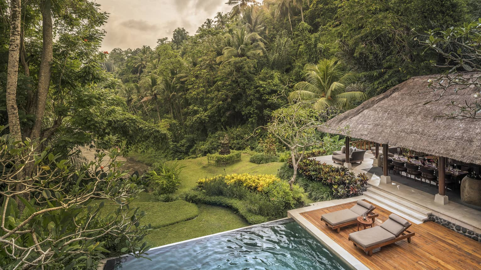 A villa with cushioned chairs and an infinity pool overlooking a river in Bali