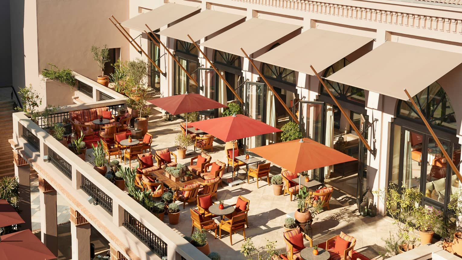 Aerial view of sunny patio with dining tables, chairs, orange umbrellas