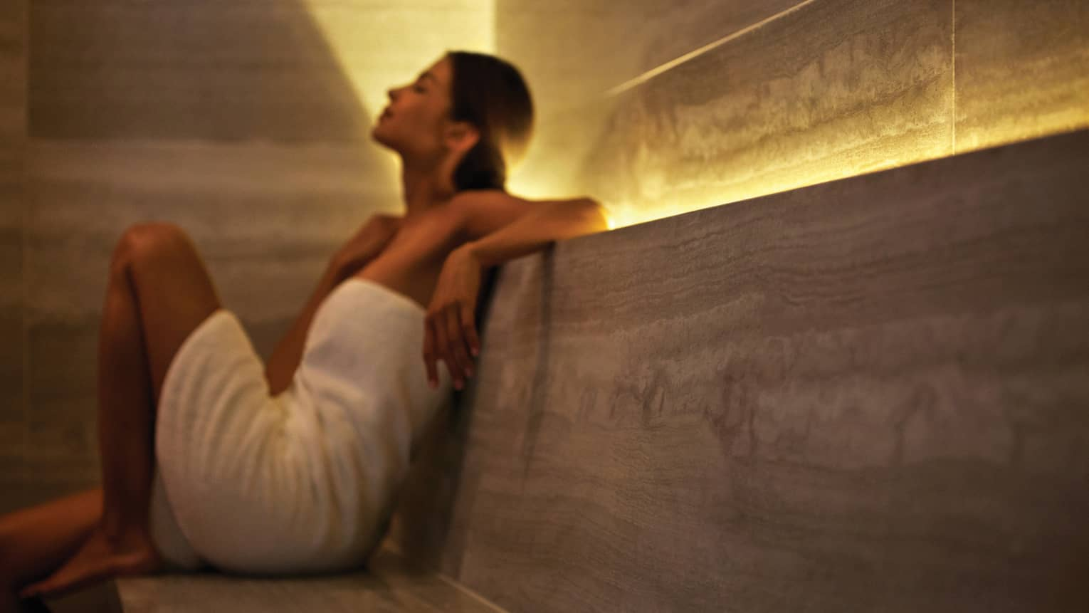 Woman wearing white towel leans back against spa wall