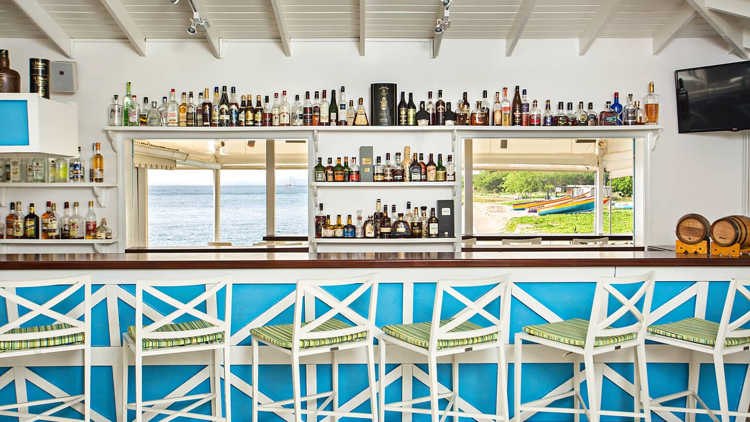 Blue and white beach bar lined with stools at 101 Rums Bar