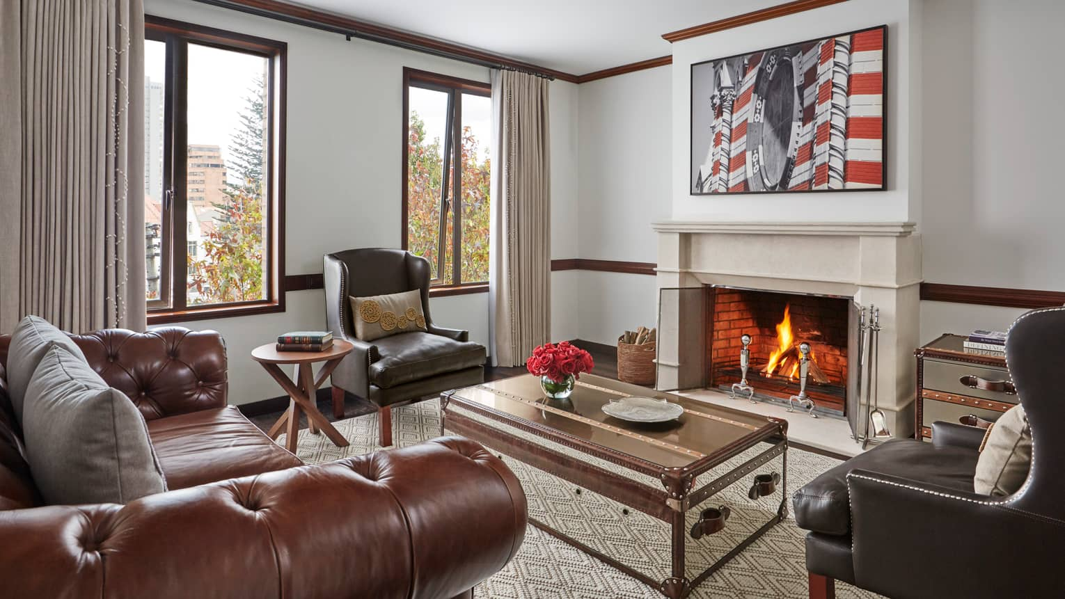 Hotel living room with brown leather sofa and armchairs trunk-style coffee table in front of roaring fireplace