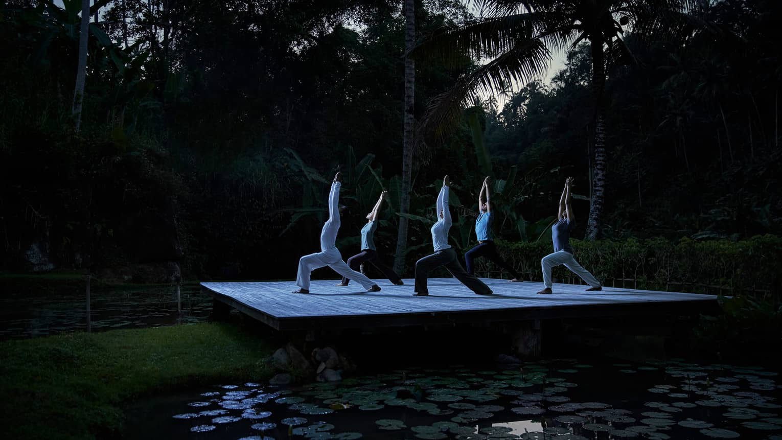 Five people kneel in yoga pose with arms above head on wood platform in forest at night