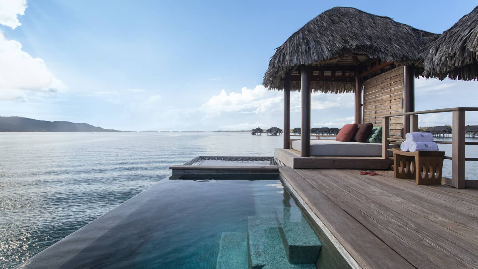 Private deck of Bungalow, with infinity pool and thatched-roof sun bed