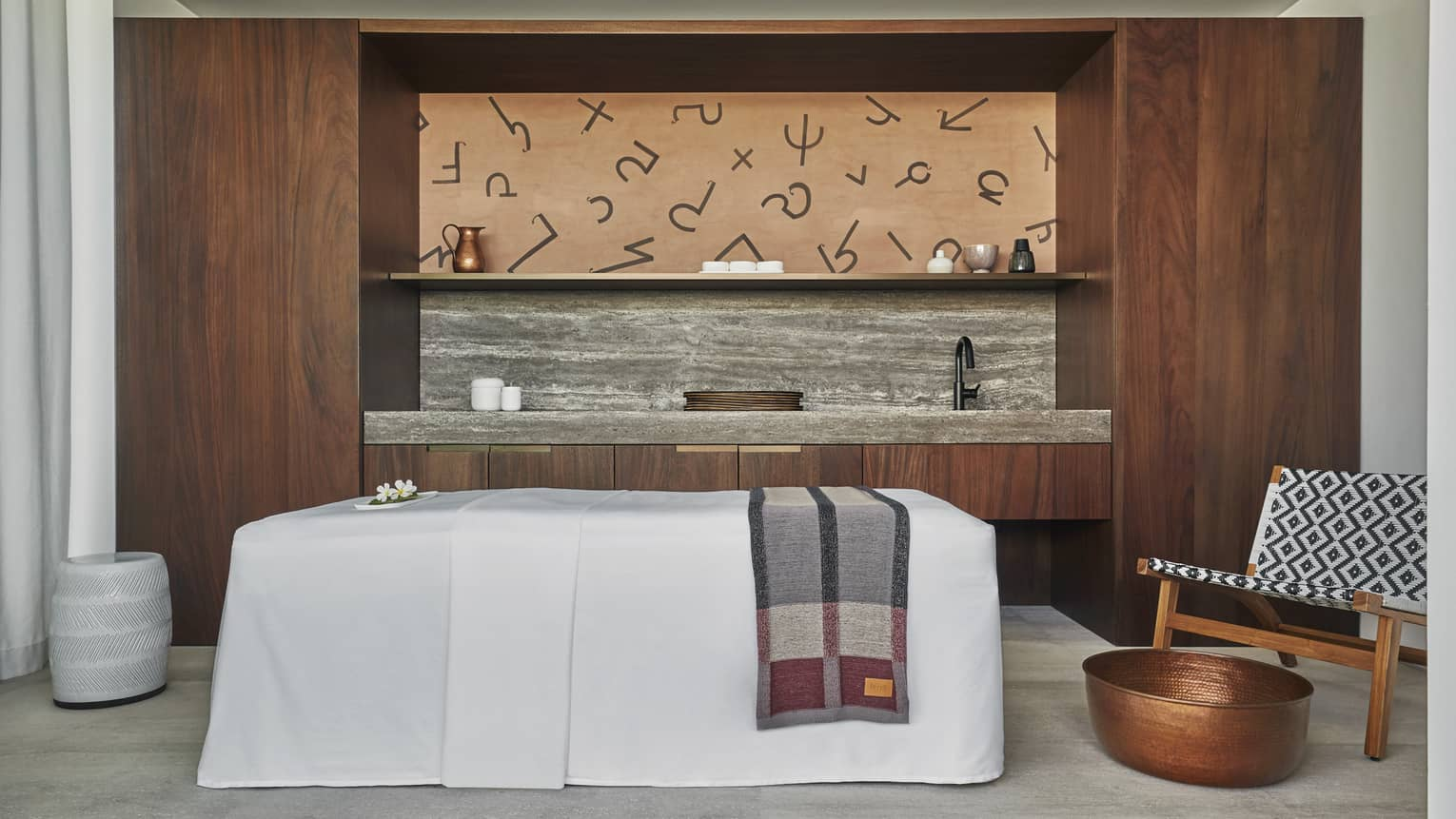 A Four Seasons Resort Los Cabos spa room is decorated with a walnut wooden accent wall with a gray concrete shelf, a mid century modern chair with a blue and white tribal pattern and a massage table covered with a white cloth