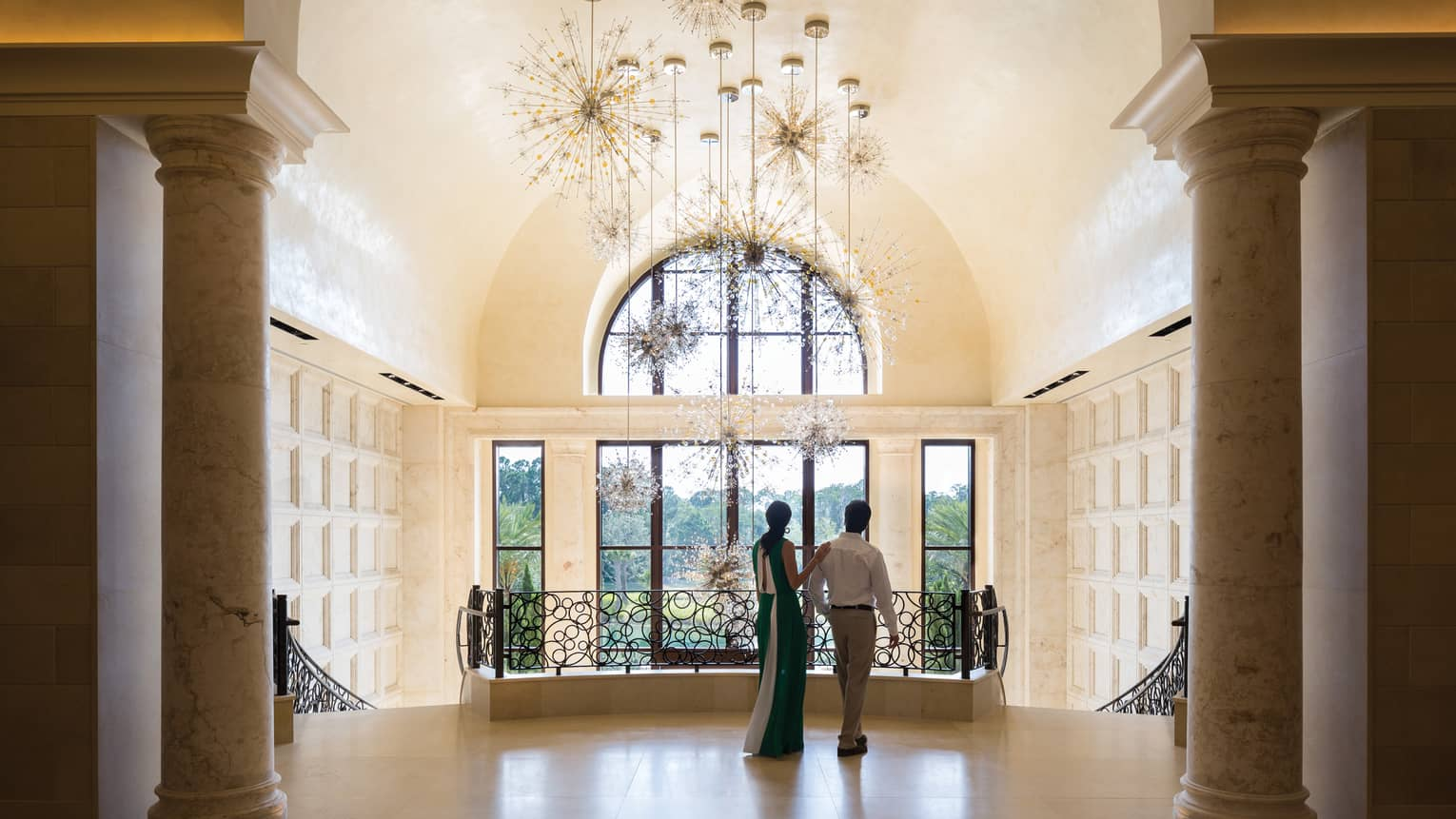 Back of man, woman wearing long dress at top of marble staircase by modern chandelier, windows