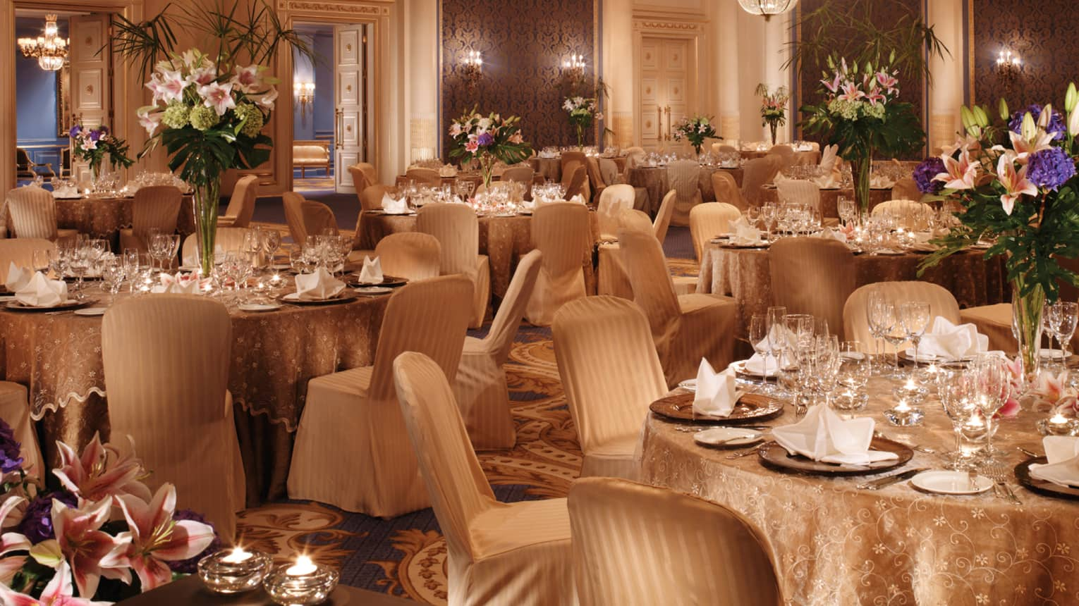 Elegantly set tables with gold tablecloths, flowers in ballroom with textured blue panels chandeliers