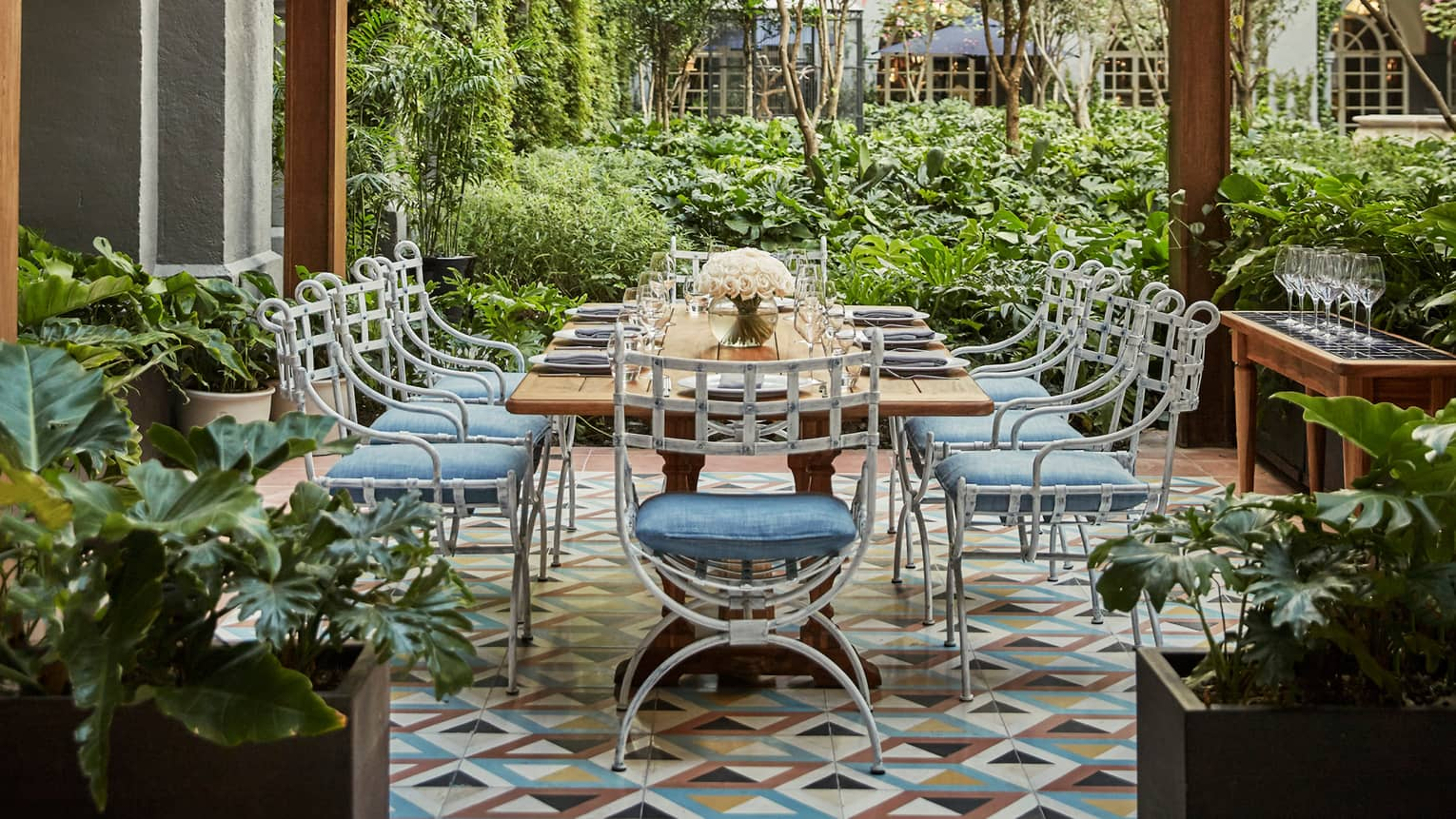 Long iron outdoor dining table, chairs with blue cushions on Zanaya garden patio
