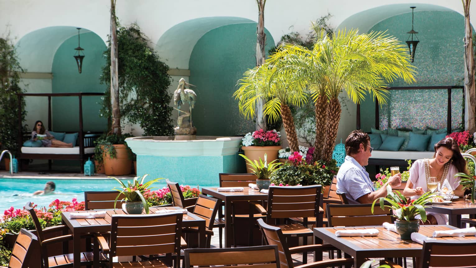 Couple dines on sunny patio by palms, tables, man swimming in outdoor swimming pool