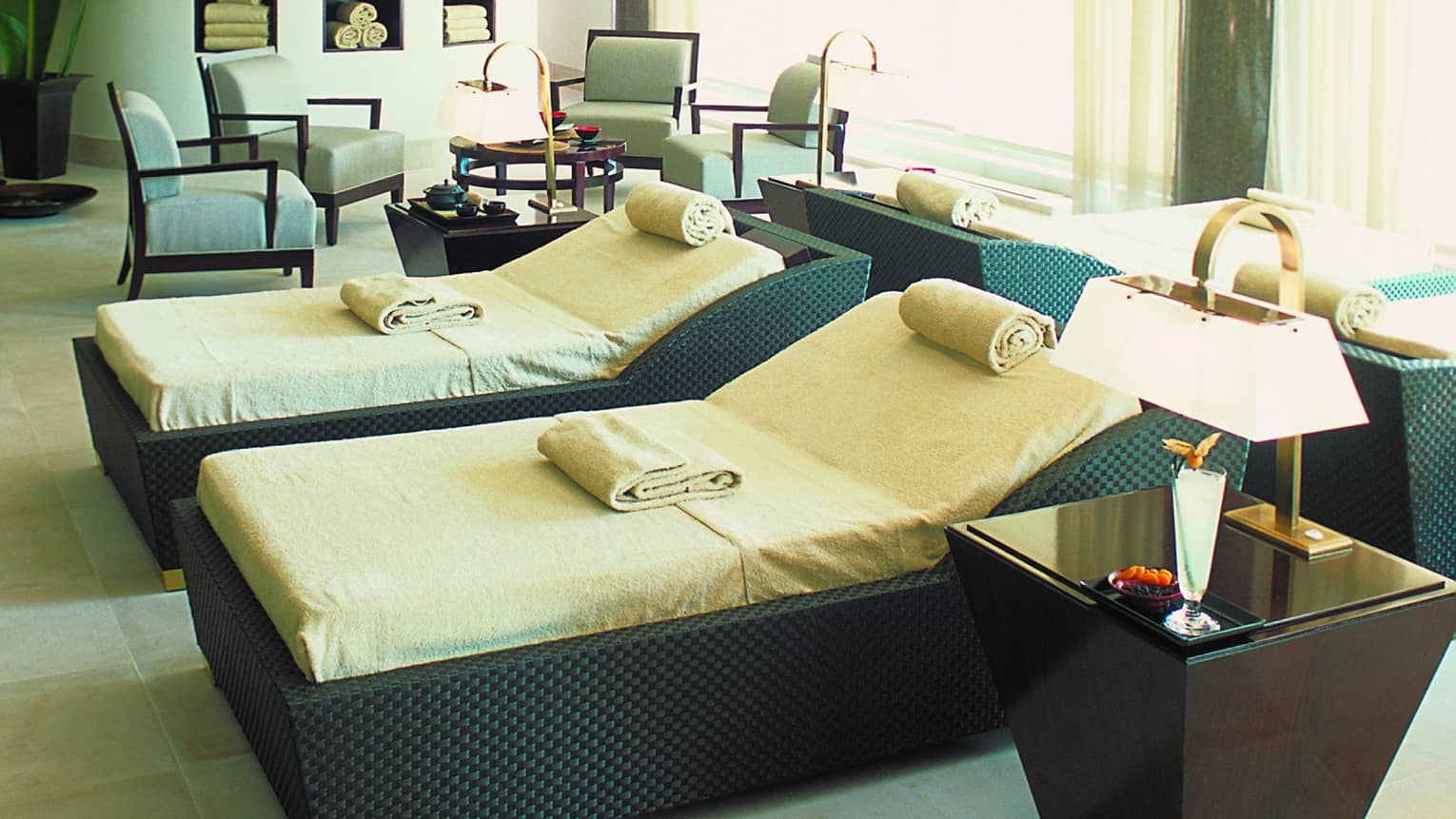 Two large black wicker spa beds with cushions, rolled towels beside table with lamp, seating area in background