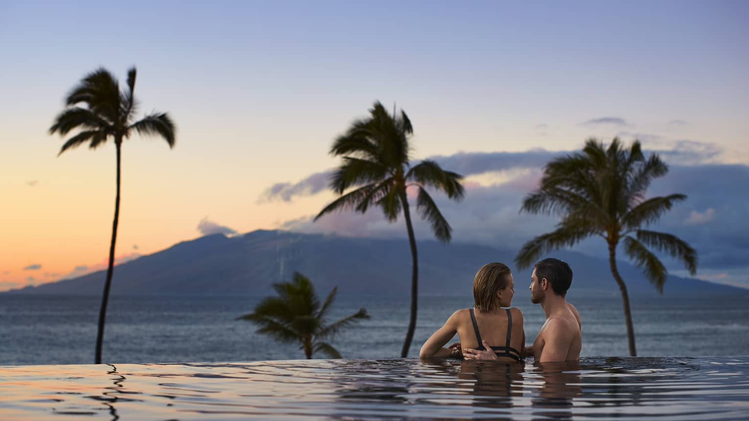 A man and woman stand close together in the serenity pool, overlooking sunset over the ocean