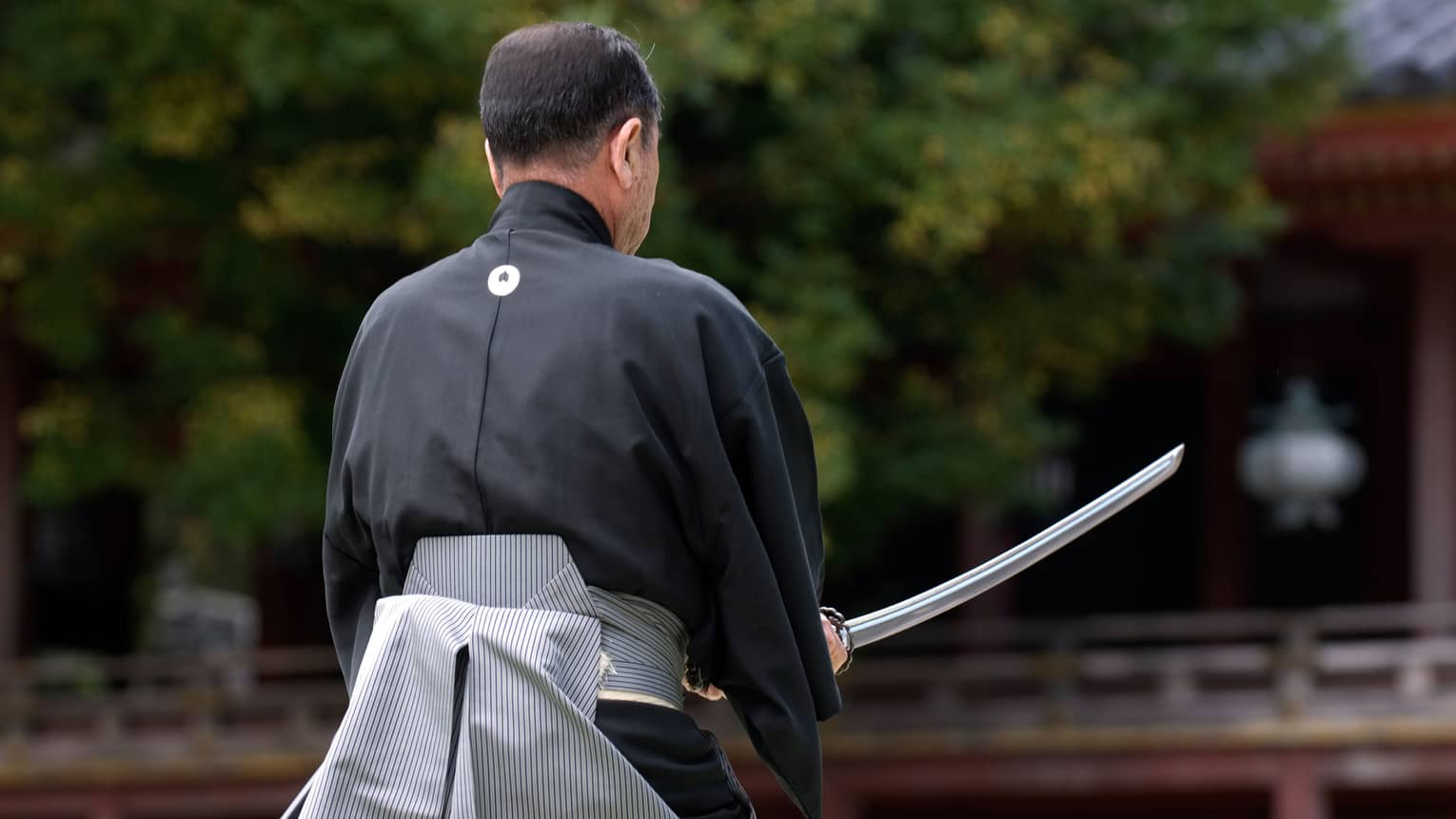 Back of man holding traditional sword in garden