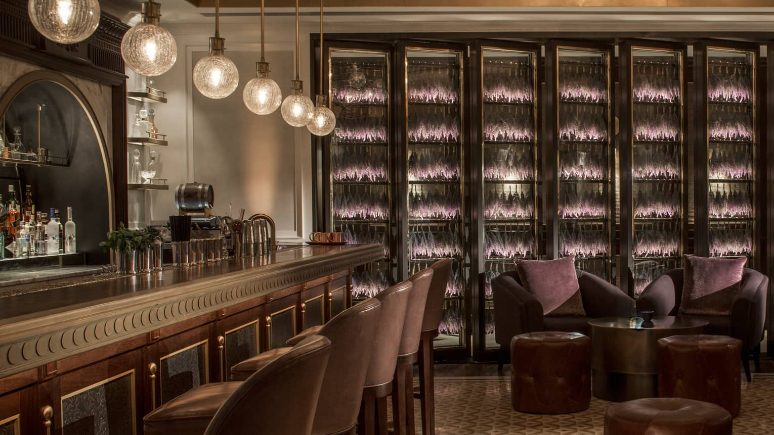 The bar at La Capitale with globe lighting, dark wood paneling, brown leather chairs and purple accents