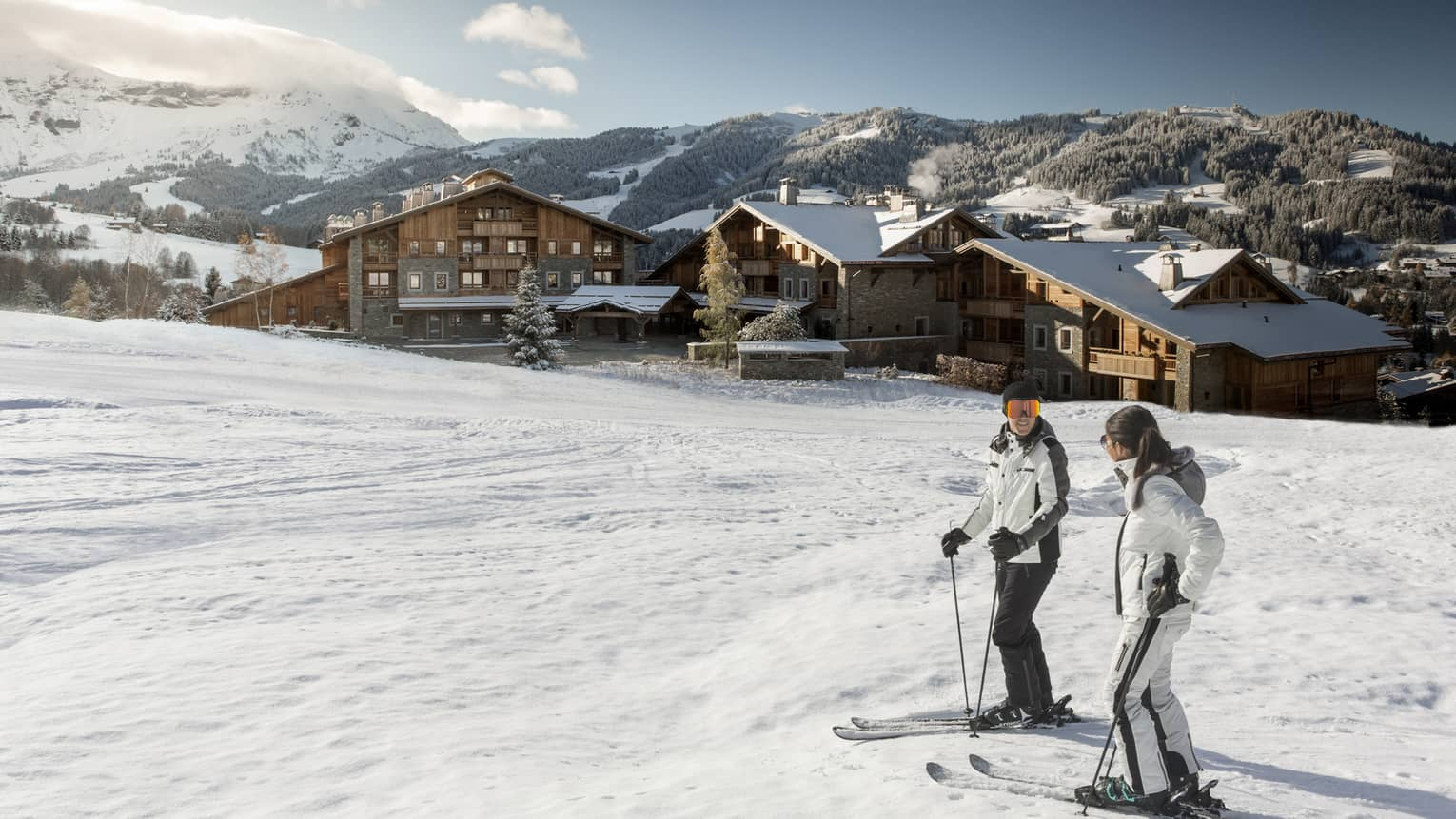 Man, woman on skis at top of snowy hill, Four Seasons Hotel Megeve in background