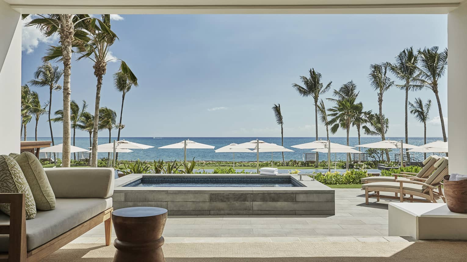 Pacific Suite open to wall to patio with stone plunge pool, lounge chairs, ocean views