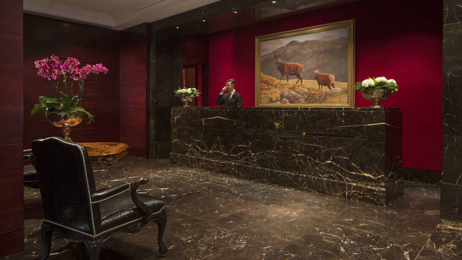 Black marble floor, reception desk, staff answers phone under large painting of elk
