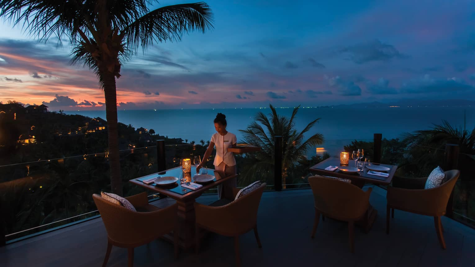 Waitstaff sets the table on outdoor terrace at Koh Thai Kitchen in Koh Samui, view of palm trees and Gulf of Thailand