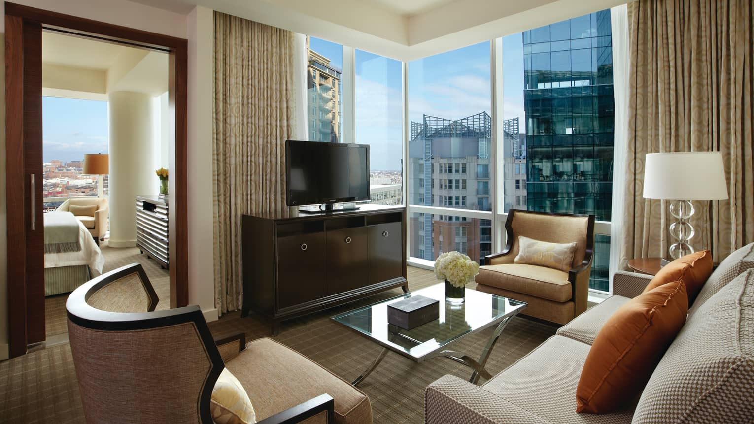 Executive Suite living room sofas, chairs, TV, corner glass windows