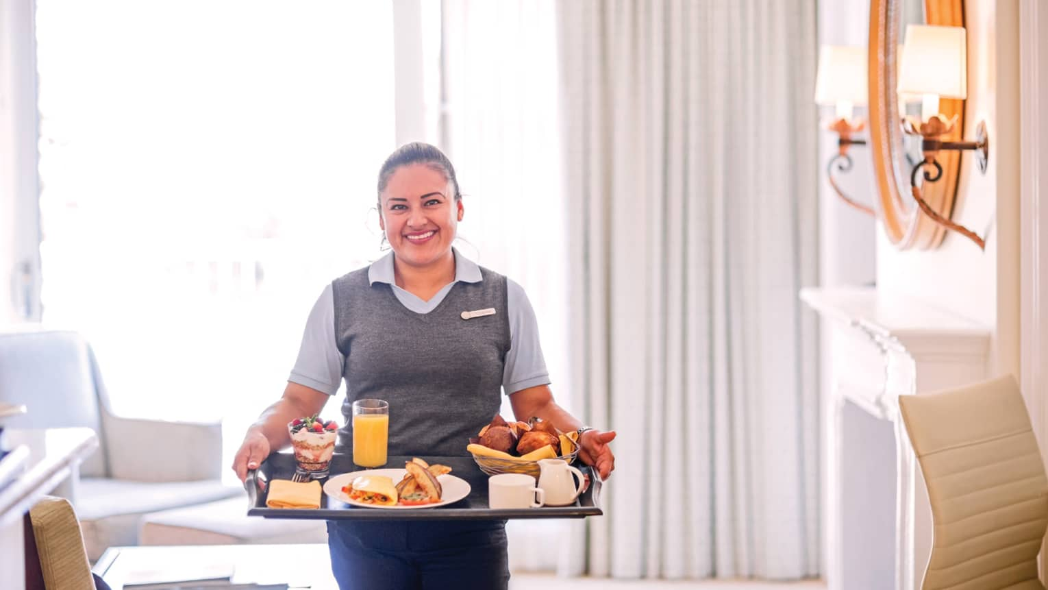 Smiling server carries in-room breakfast tray in elegant white hotel room