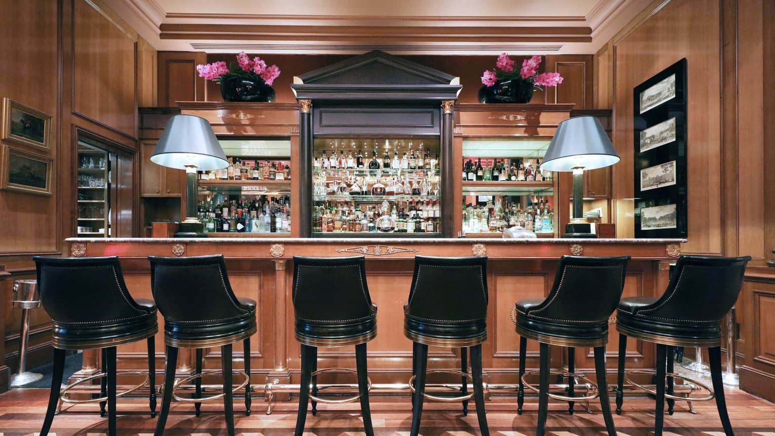 Black bar stools along Le Bar rail, liquor display, purple flowers