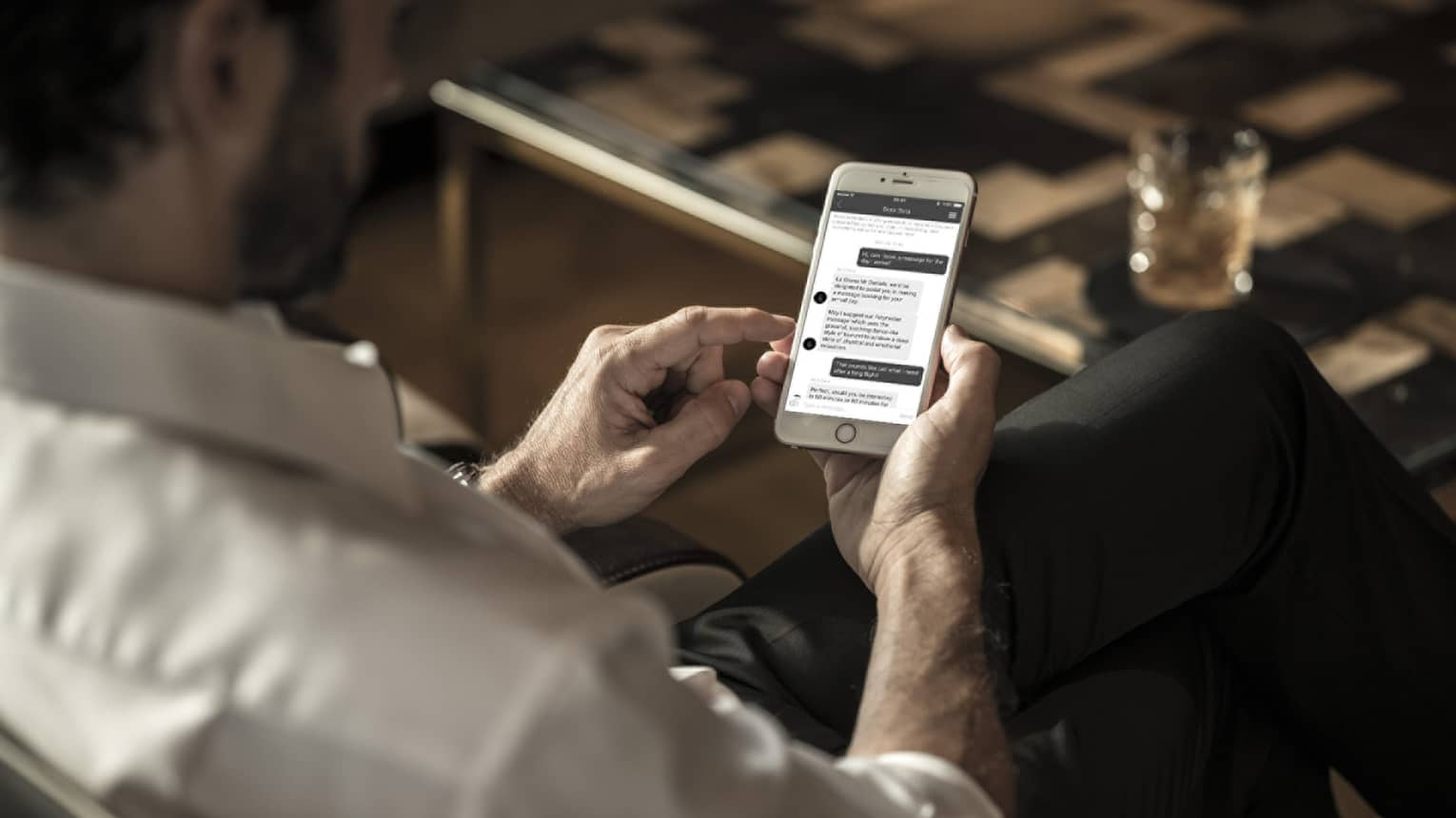 Man wearing suit looks down at text messages from spa on smart phone in lounge