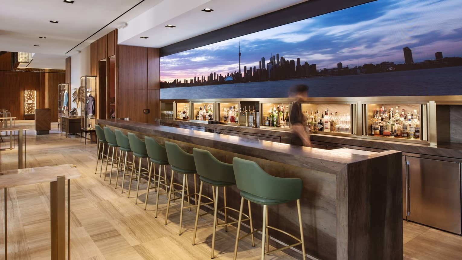 Upholstered chairs lined at a bar with a large image of the skyline