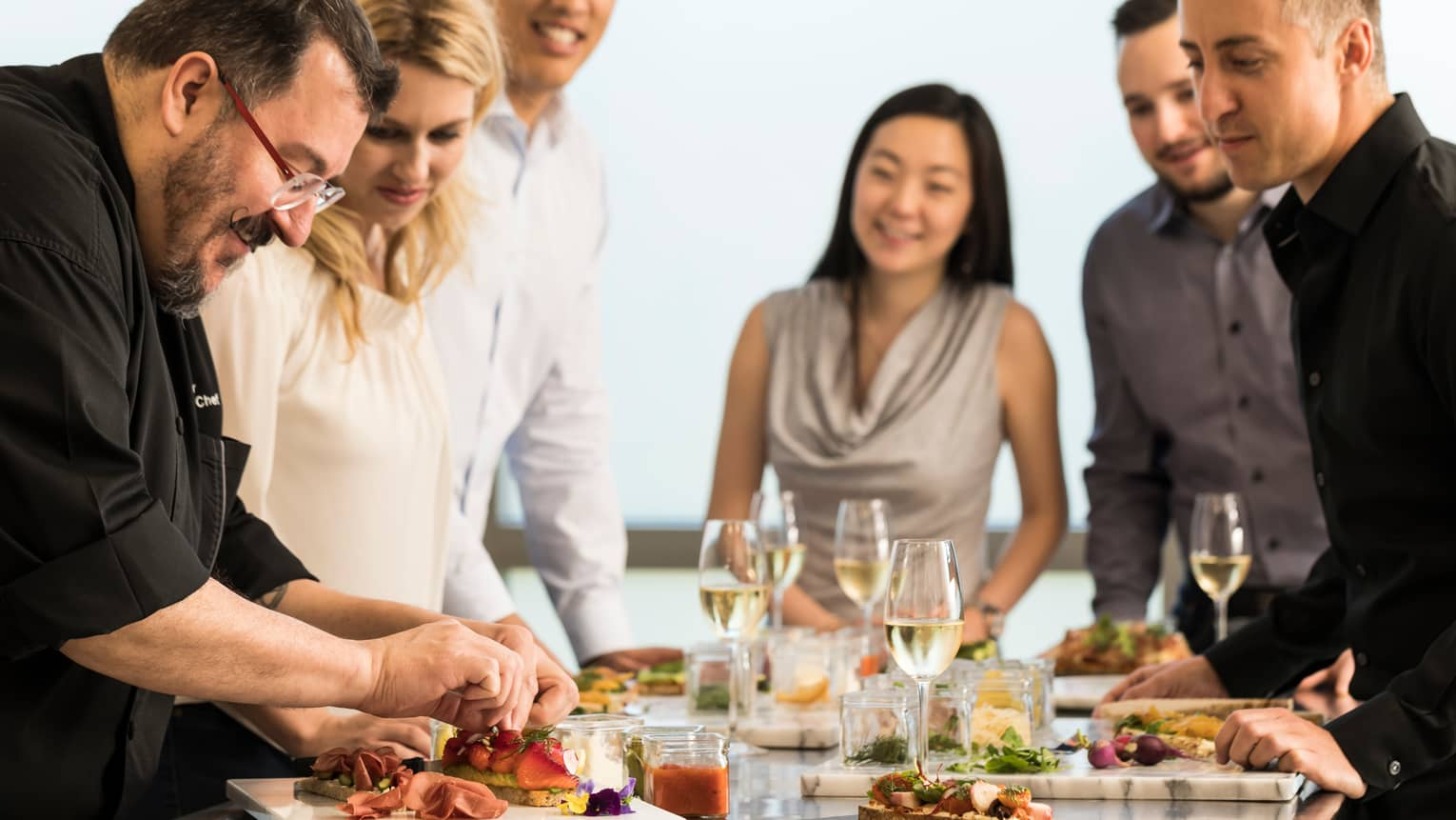 Chef assembles food at counter with smiling group of friends, white wine in glasses