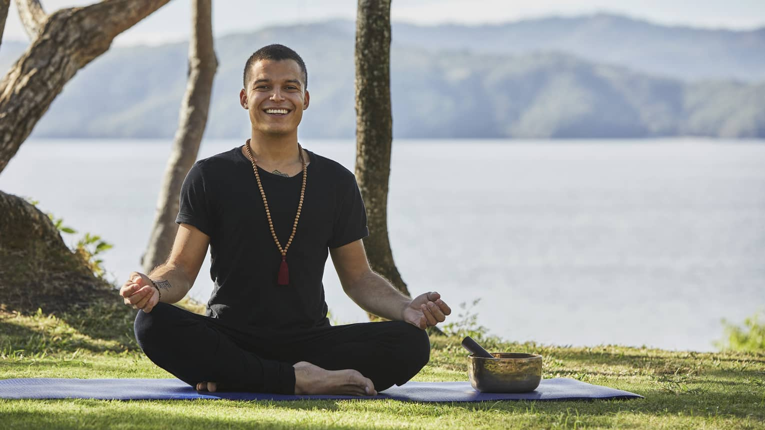 A yoga instructor smiles as he sits on a mat outside in front of a mountain range