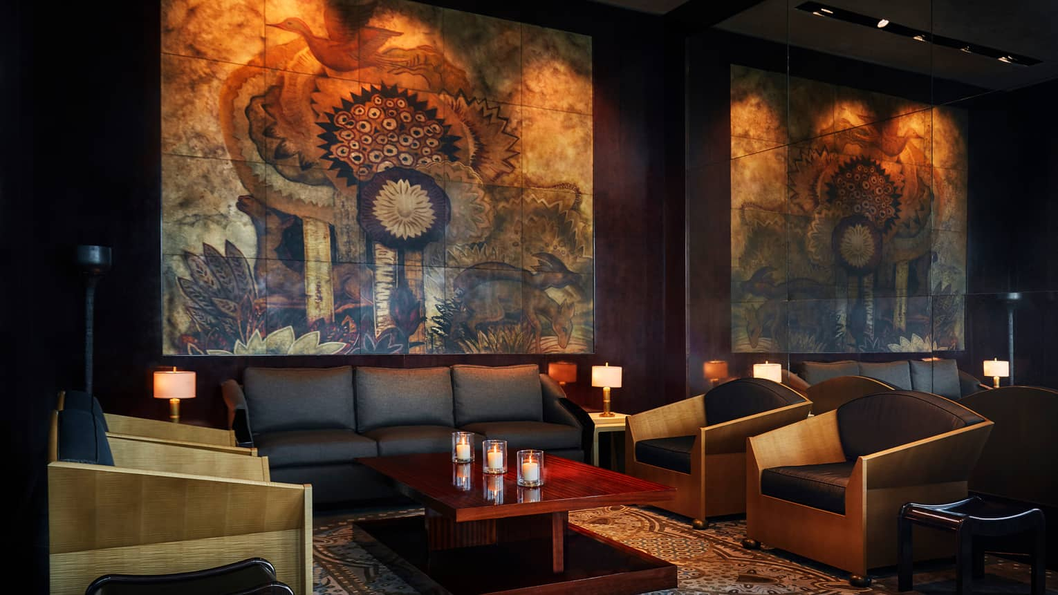 CUT by Wolfgang Puck dimly-lit lounge area with leather sofas and chair, large mural