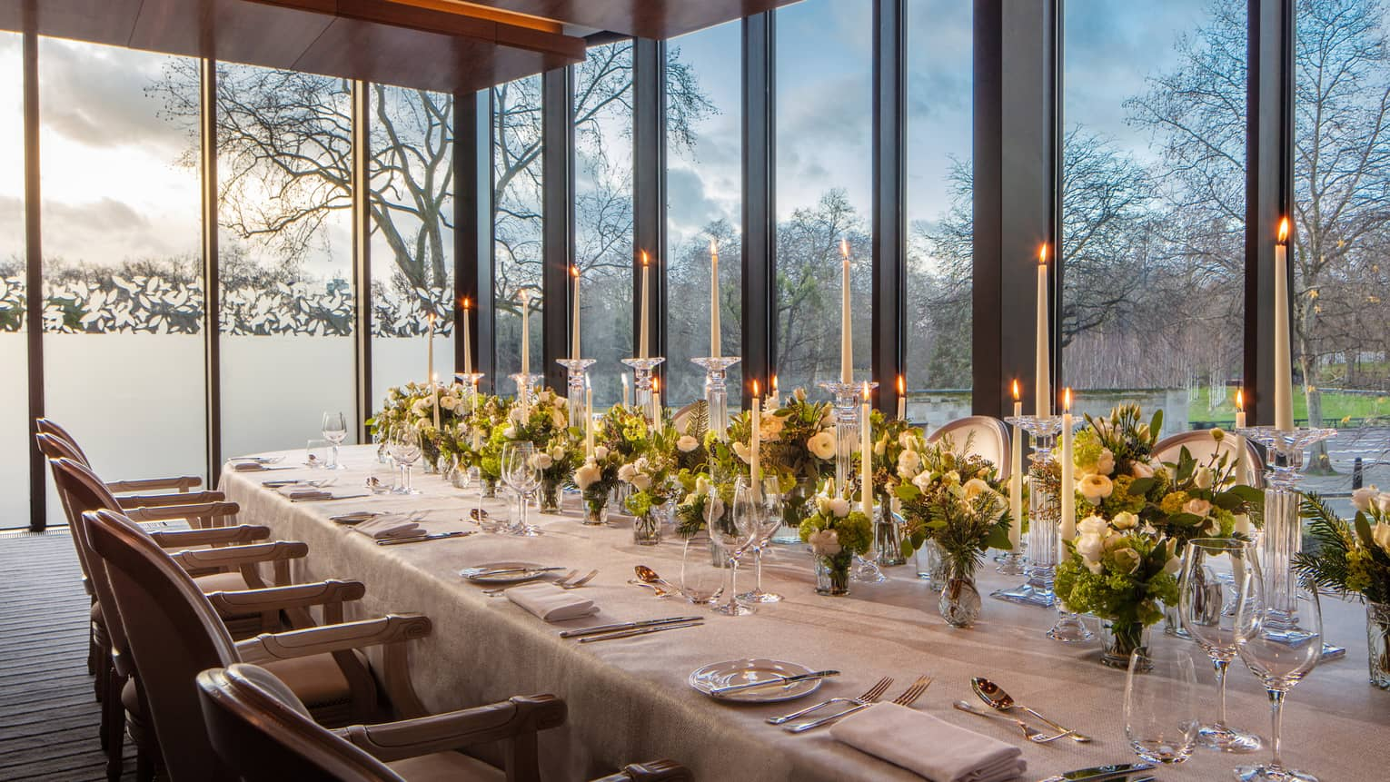 Meeting room set for dinner with white linens, tall tapered candles, green floral arrangements, and plenty of natural light