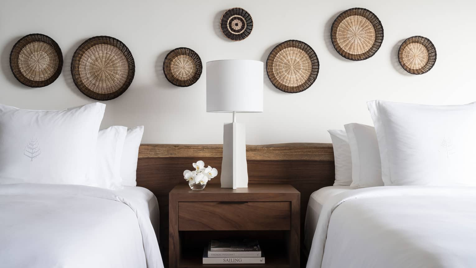 Wood nightstand and white lamp between twin beds, decorative rattan discs on wall