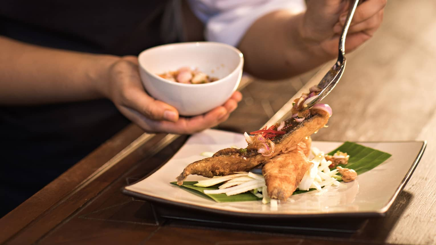 Woman spoons sauce onto Pra Ram Long Song fried fish on plate