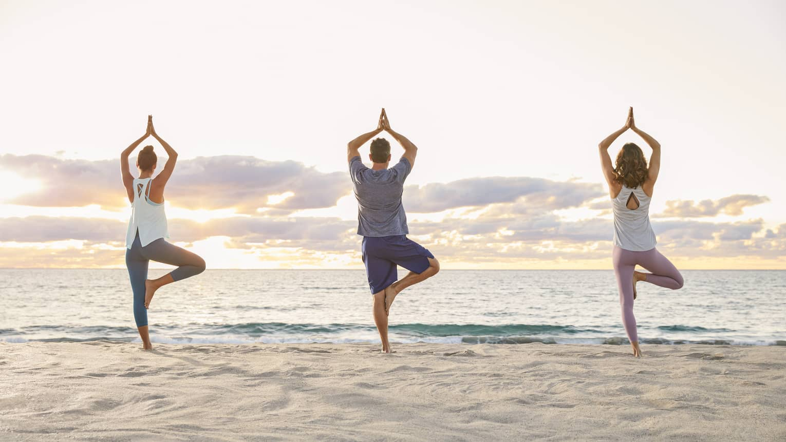 Backs of three people standing in yoga pose on sand beach at sunrise