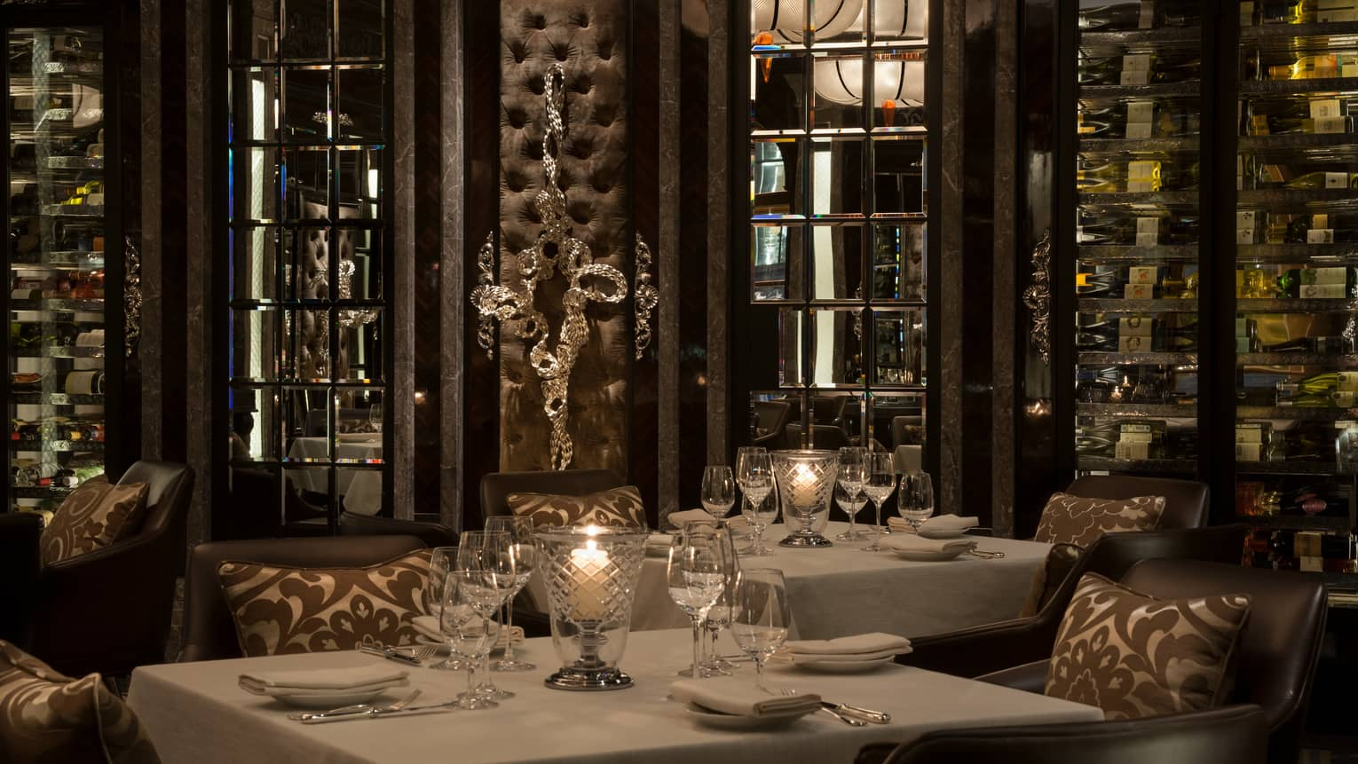 Candles glow in crystal votives on dining tables with white tablecloths in dark Percorso restaurant