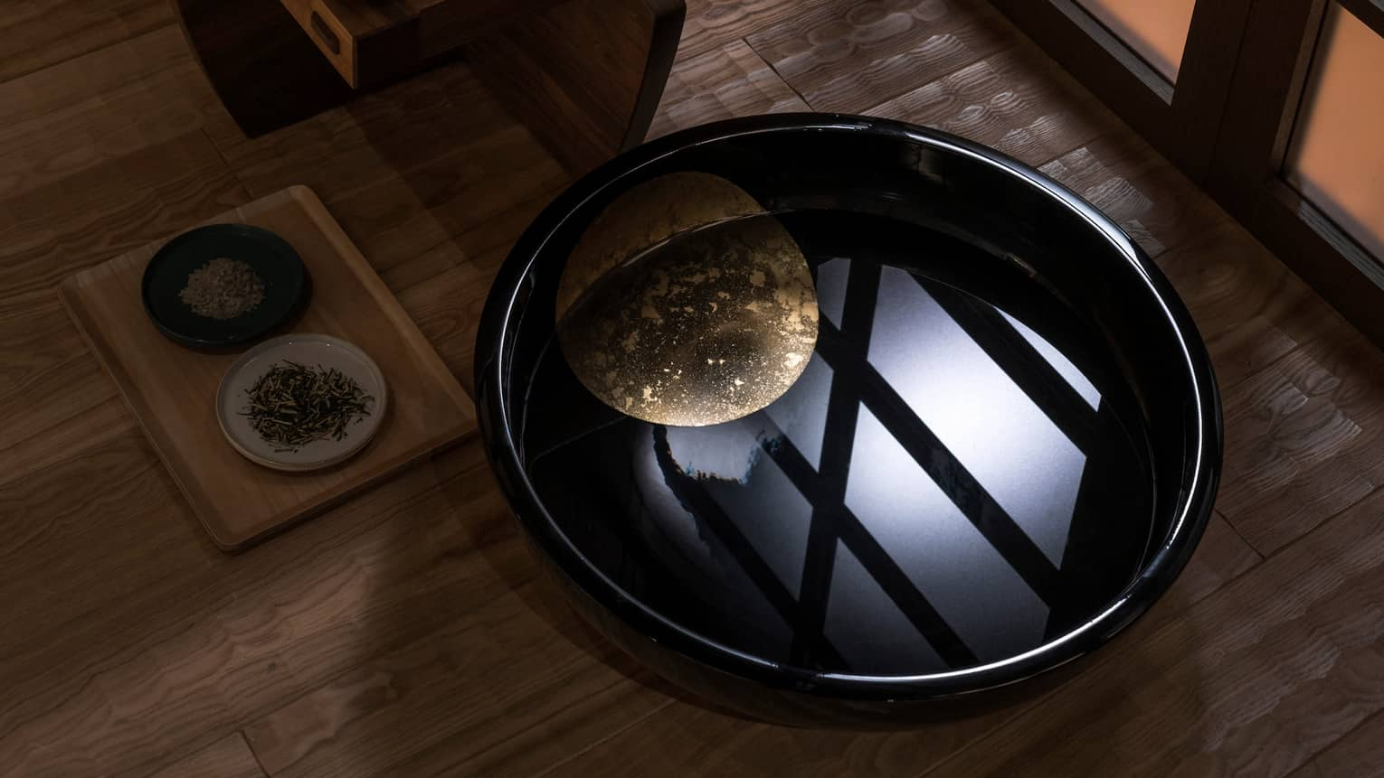 Light reflected in black bowl with water in spa