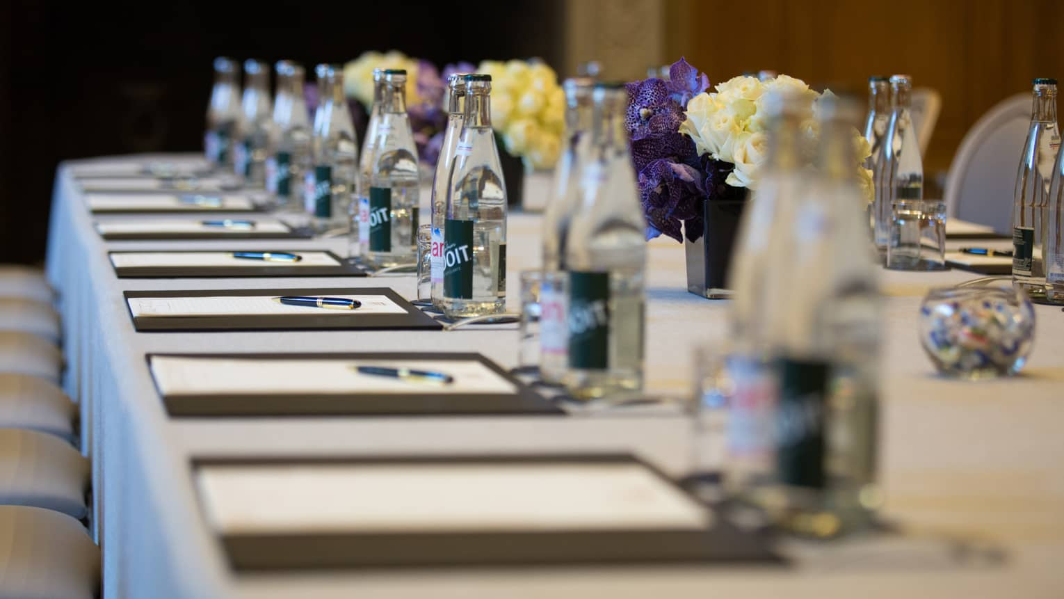 Row of meeting agendas, glass bottles, small vases with flowers on boardroom table