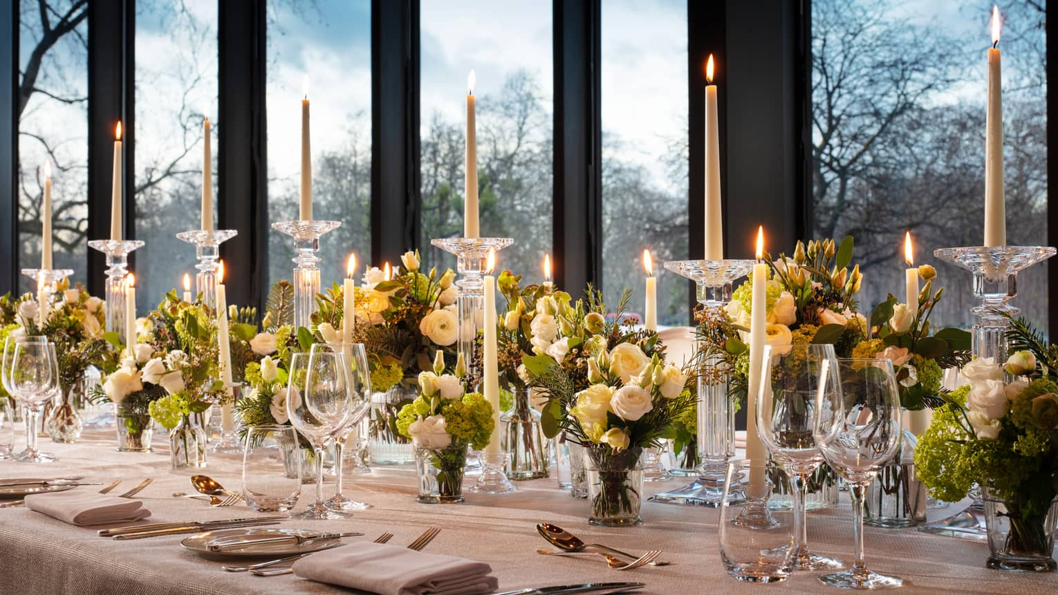 Closeup shot of meeting room table set with tall tapered candles and green floral arrangements against a window backdrop