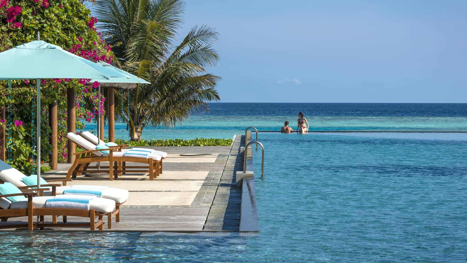 Resort infinity pool leading out to turquoise ocean, wooden lounge chairs and light blue umbrellas