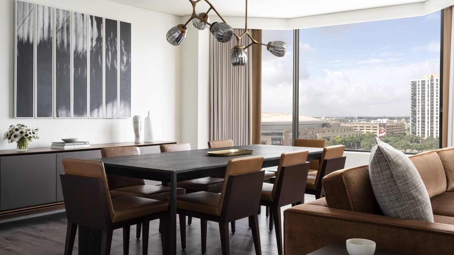 Dining room with table and eight chairs, modern hanging lamp, large window with city view