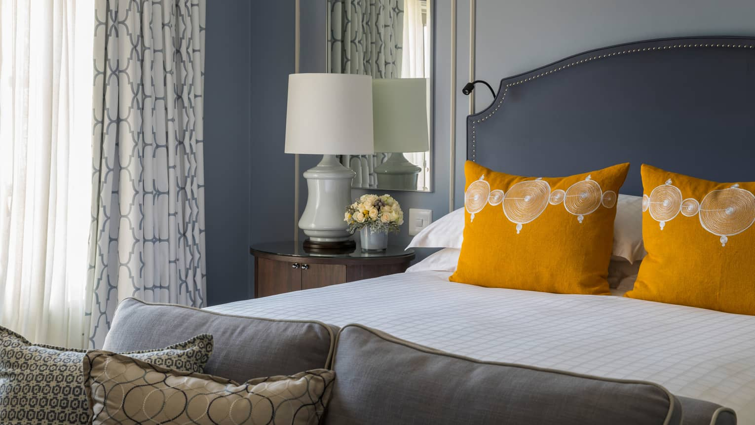 One Bedroom Suite bed with bright yellow accent pillows, white lamp on nightstand in front of mirror