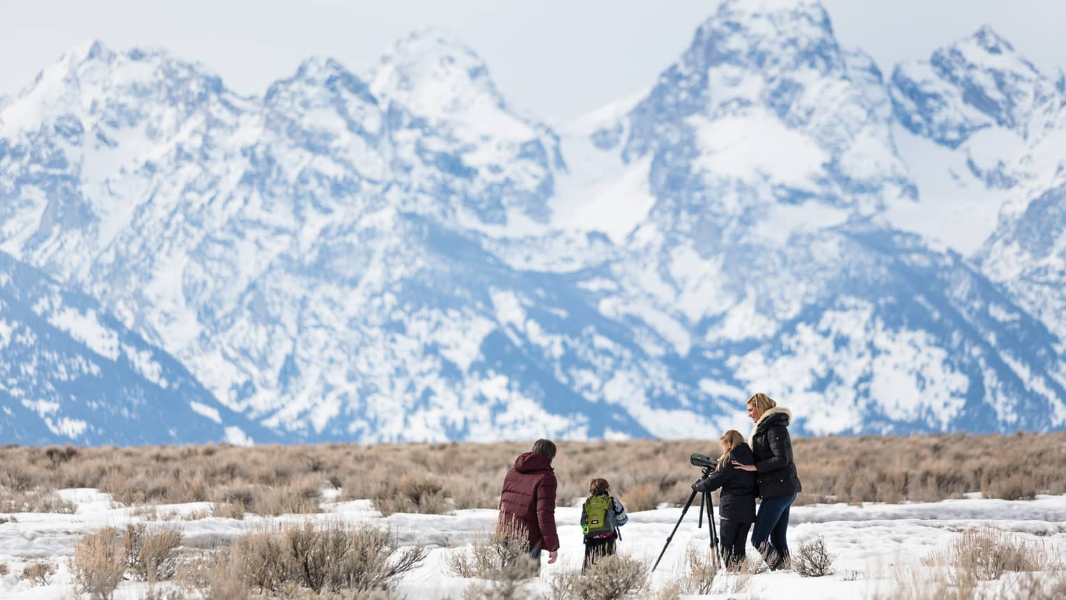Family in snowy field with camera on tripod pointed at towering mountains