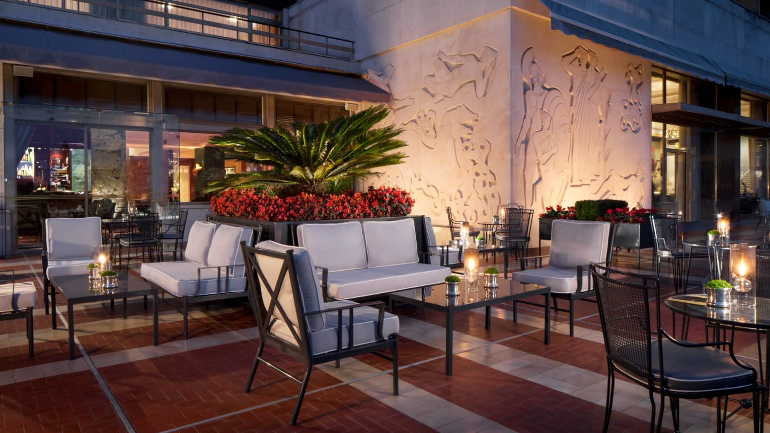 Ritz Bar outdoor patio lounge at night with cushioned chairs and loveseats around candle-lit cocktail tables