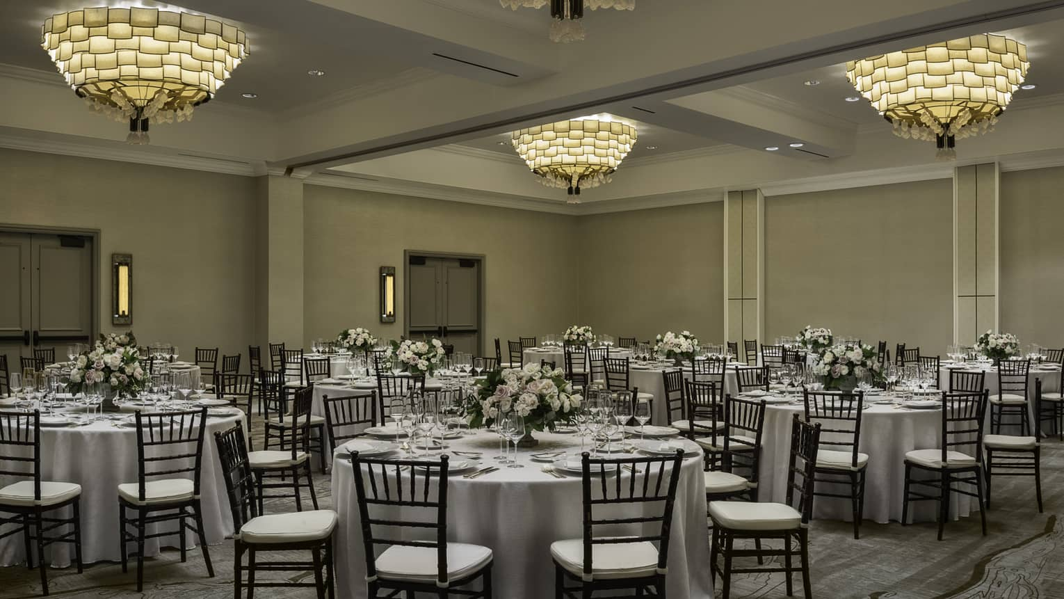 Large round banquet dining tables and chairs under three small chandeliers