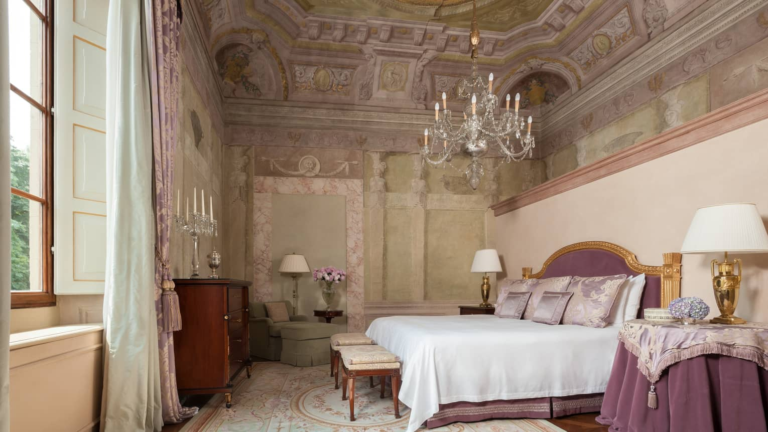 Frescoed Executive Suite bed with purple velvet headboard, nightstand with cloth under chandelier, vaulted ceiling