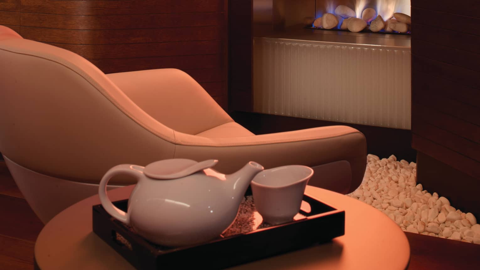 Modern white tea pot, cup on tray by leather chair, fireplace in background