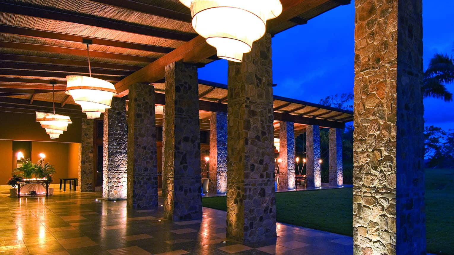 Large chandeliers hang from roof over outdoor path lined with stone pillars at night