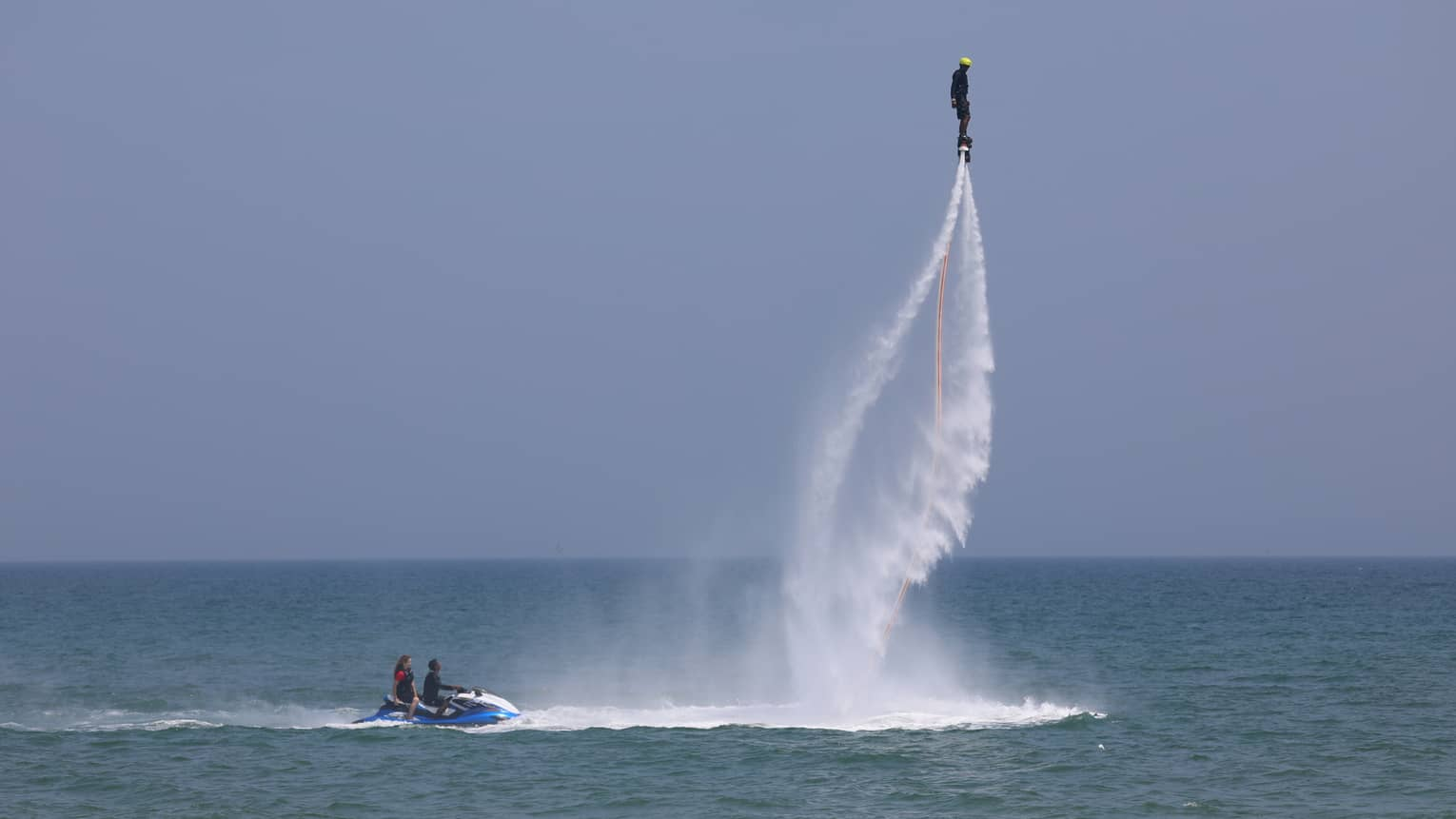 Person in extreme jet-pack with water trails, high above ocean, two jet skiers