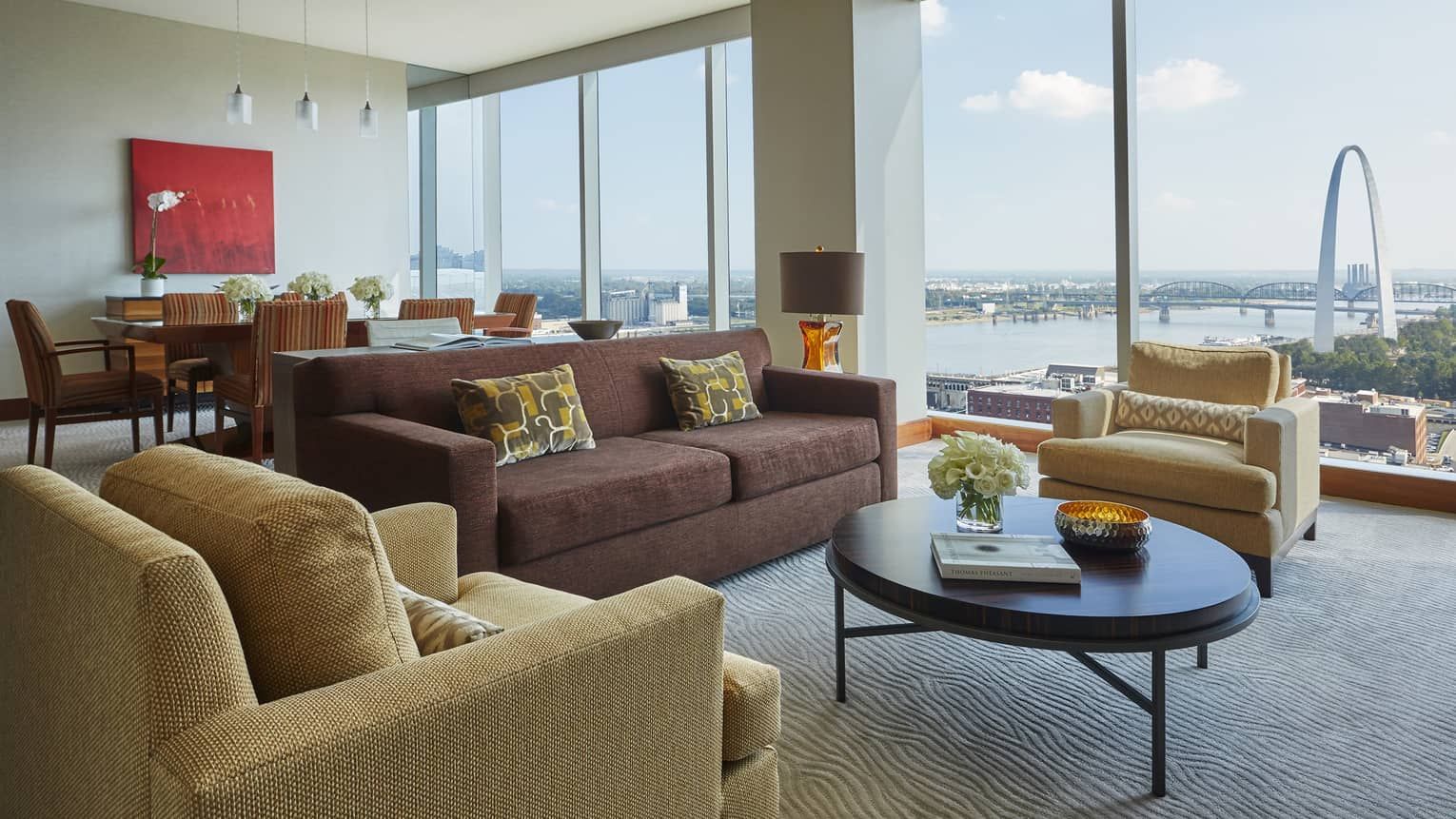 Luxury suite living room with burgundy sofa, yellow armchairs, round coffee table, tall windows with arch view