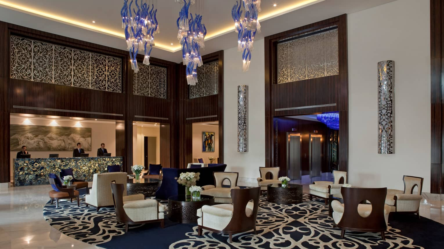 Four Seasons Buenos Aires hotel elegant lobby with armchairs on blue-and-white carpet, under modern chandeliers
