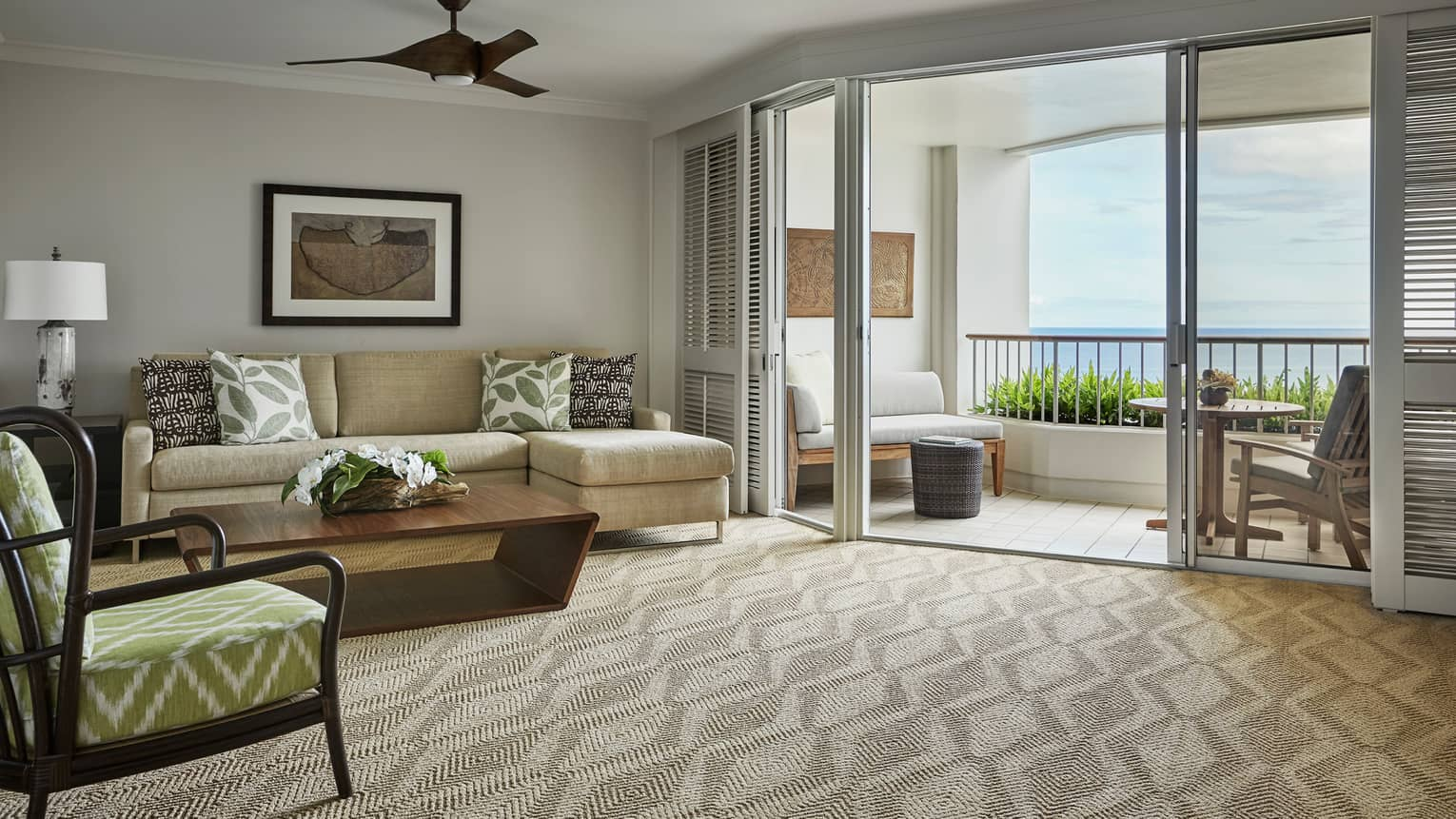 Oceanfront Suite living room with L-shaped sofa, chair on carpet, shutters on patio door